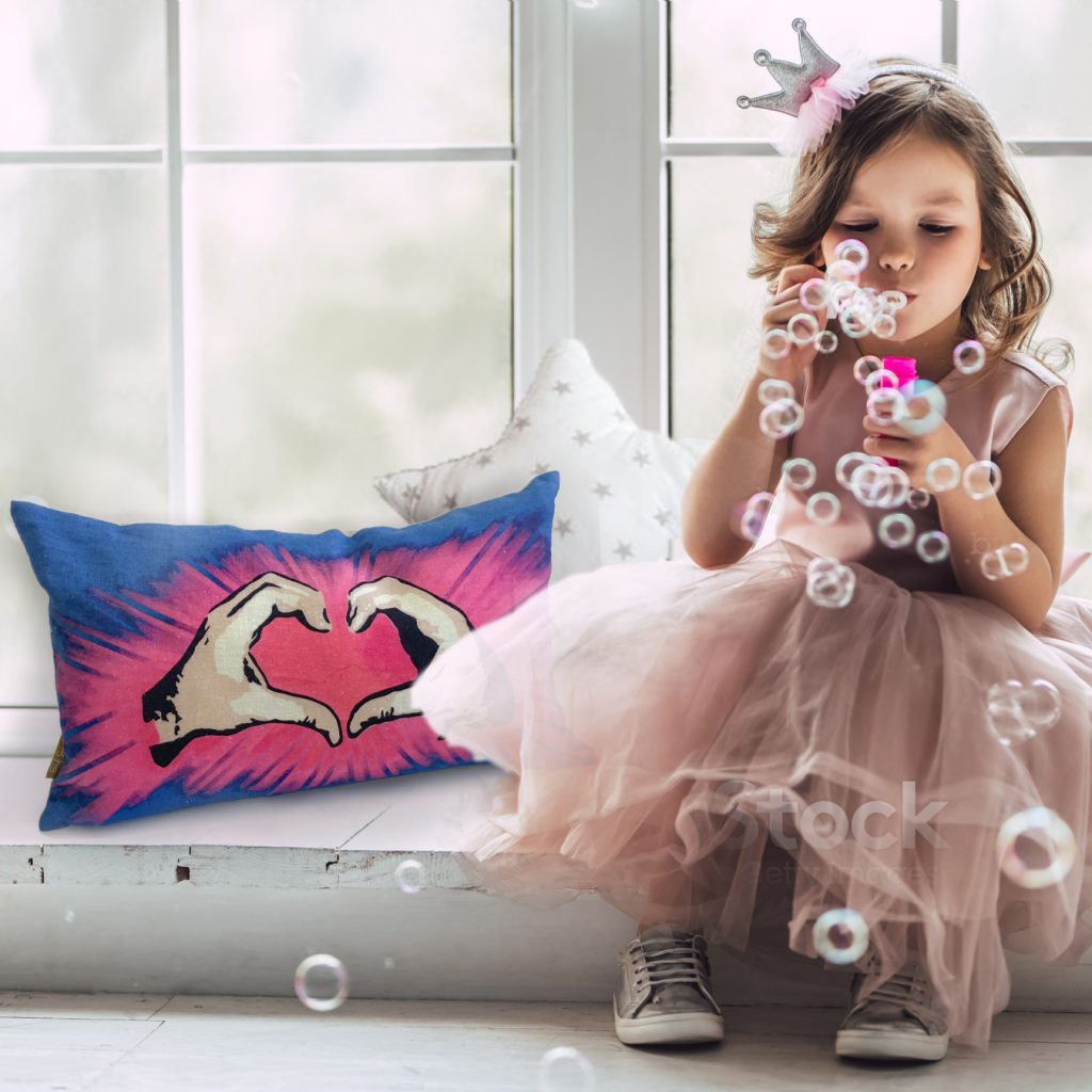 Little girl in party dress with Handful of Love cushion from Streetart Society.