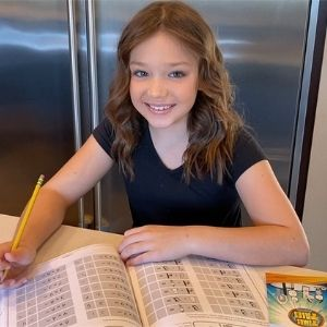 Girl memorizing the times tables with the Times Tales workbook