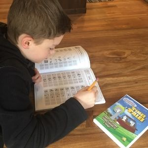 Boy using the Times Tales workbook and DVD to memorize multiplication facts.