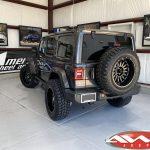 "2020 Gray JL Jeep 2.5"" Rough Country Lift 20"" Ballistic Off-road Machete Wheels Gloss Black 35x12.50R20 tires left rear angle"
