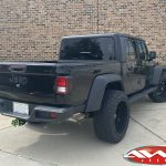 "2020 Black Jeep Gladiator 2.5″ Rough Country lift 22×12 Hostile H114 ""Fury"" wheels asphalt 35″ tires left rear angle"